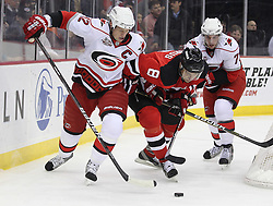 Feb 16; Newark, NJ, USA; Carolina Hurricanes center Eric Staal (12) and New Jersey Devils right wing Dainius Zubrus (8) battle for a loose puck during the first period at the Prudential Center.