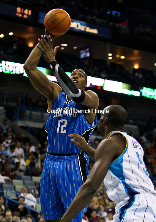 Feb 26, 2010; New Orleans, LA, USA; Orlando Magic center Dwight Howard (12) shoots over New Orleans Hornets center Emeka Okafor (50) during the first half at the New Orleans Arena. The Hornets defeated the Magic 100-93. Mandatory Credit: Derick E. Hingle-US PRESSWIRE