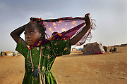 "CAMP OURE CASSONI, CHAD - AUGUST 31:  A child refugee from the Darfur region of Sudan wears a protective Islamic amulet called a ""hijab"" as she walks near her family's tent home in the Oure Cassoni refugee camp located in northeastern Chad. More than 18,000 refugees have already taken up residence in the camp and aid workers warn that if the situation in Darfur does not improve soon, thousands more Sudanese could flood into neighboring Chad, quickly overwhelming already strained resources to feed and house them."