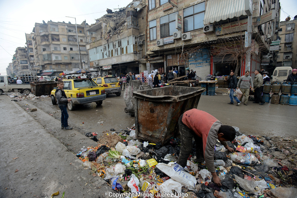 Aleppo, Syria, December, 2012.  A boy searches in a pile of garbage for something to eat in the neighborhood of Tarik Albab. The city is suffering from a lack of services at the beginning of a very crude winter. Some sectors have survived with out water or electricity for more than 45 days. (Photo by Miguel Juárez Lugo)
