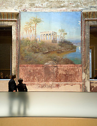 Visitors looking at mural on wall of newly reopened Neues Museum on Museumsinsel in Berlin