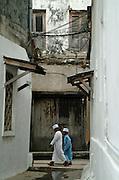 Africa. Tanzania. Zanzibar.  Stone Town..Boys wearing traditional Khanzus -white robes..CD0011