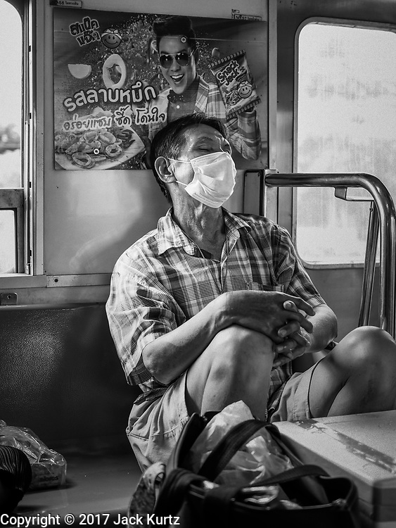 30 MAY 2017 - CHACHOENGSAO, THAILAND: Passengers on a Bangkok-Chachoensao commuter train. Chachoengsao is a provincial town about 50 miles and about an hour by train from Bangkok. The train from Chachoengsao to Bangkok takes a little over an hour but traffic on the roads is so bad that the same drive can take two to three hours. Thousands of Thais live outside of Bangkok and commute into the city for work on trains, busses and boats.         PHOTO BY JACK KURTZ