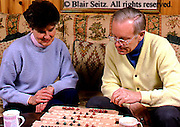 Active Aging Senior Citizens, Retired, Activities, Elderly Couple Play Table Game at Home