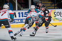 KELOWNA, CANADA - FEBRUARY 28: Connor Rankin #26 of Calgary Hitmen checks Cole Linaker #26 of Kelowna Rockets as he skates with the puck during the second period on February 28, 2015 at Prospera Place in Kelowna, British Columbia, Canada.  (Photo by Marissa Baecker/Shoot the Breeze)  *** Local Caption *** Connor Rankin; Cole Linaker;