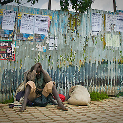 A homeless man sits against tempory wall covered with posters for job offers and musical concerts.  Behind this wall land is being cleared for new apartment buildings.