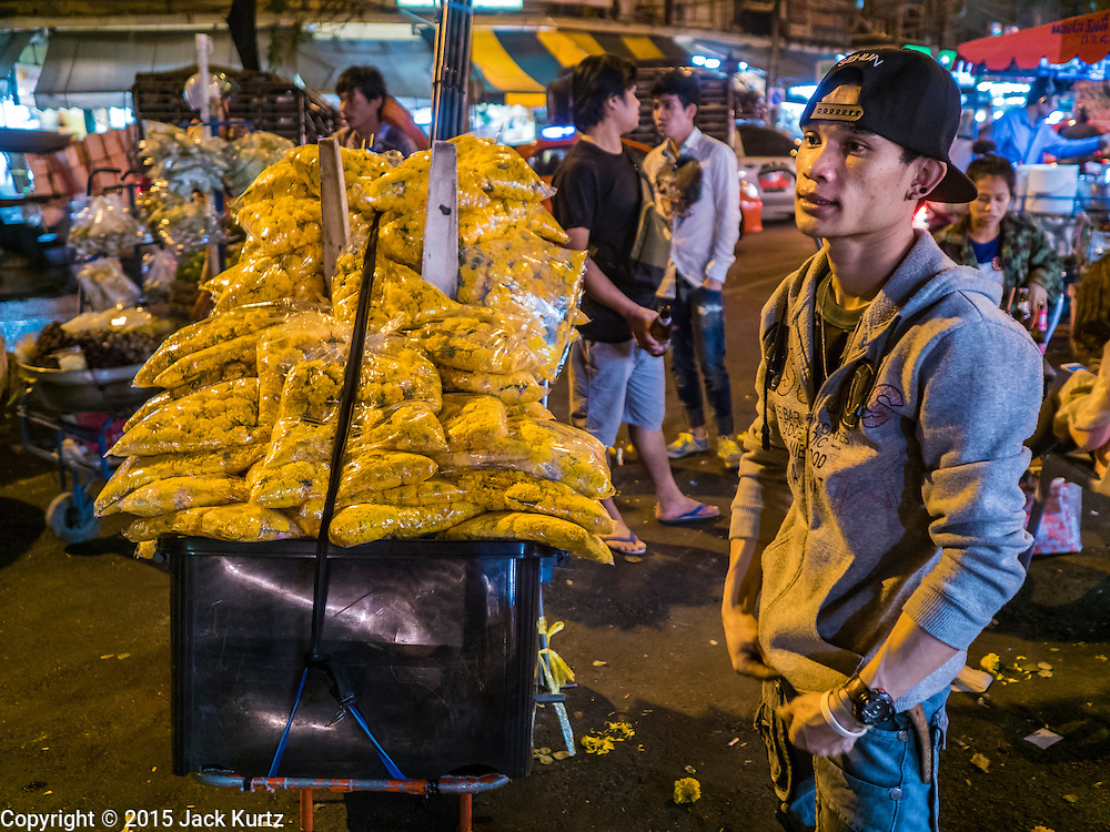 """21 DECEMBER 2015 - BANGKOK, THAILAND:  A marigold vendor on the street in front of Pak Khlong Talat, also called the Flower Market. The market has been a Bangkok landmark for more than 50 years and is the largest wholesale flower market in Bangkok. A recent renovation resulted in many stalls being closed to make room for chain restaurants to attract tourists. Now Bangkok city officials are threatening to evict sidewalk vendors who line the outside of the market. Evicting the sidewalk vendors is a part of a citywide effort to """"clean up"""" Bangkok.      PHOTO BY JACK KURTZ"""
