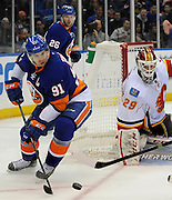 Calgary Flames goalie Reto Berra (29) defends against New York Islanders' John Tavares (91) during an NHL hockey game on Thursday, Feb. 6, 2014, in Uniondale, N.Y. (AP Photo/Kathy Kmonicek)