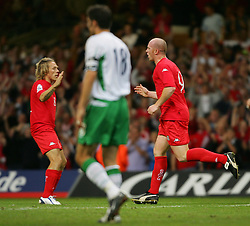 CARDIFF, WALES - Wednesday, September 8, 2004: Wales' John Hartson celebrates scoring against Northern Ireland with team-mate Craig Bellamy during the Group Six World Cup Qualifier at the Millennium Stadium. (Pic by David Rawcliffe/Propaganda)