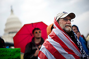 Bruce Lundeen of Harrisonburg, Va., listens to speaches on the west front lawn of the Capitol on Tueday. Hundreds of protestors with the Occupy movements gathered outside the Capitol, waving signs and chanting against a barrier of police.