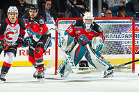 KELOWNA, BC - NOVEMBER 30:  Ilijah Colina #20 of the Prince George Cougars is checked by Carson Sass #7 as Roman Basran #30 of the Kelowna Rockets defends the net during second period at Prospera Place on November 30, 2019 in Kelowna, Canada. (Photo by Marissa Baecker/Shoot the Breeze)