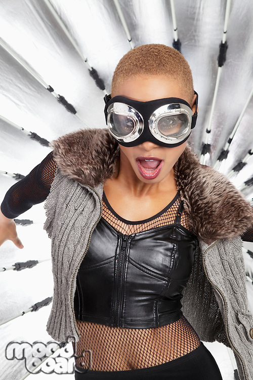Portrait of young African American woman wearing pilot goggles with open mouth