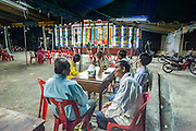 "25 JANUARY 2014 - BANG LUANG, NAKHON PATHOM, THAILAND: The audience watches the Sing Tong Teochew opera troupe during a show in a Chinese shrine in the town of Bang Luang, Nakhon Pathom, Thailand. The Sing Tong Teochew opera troupe has been together for 60 years and travels through central Thailand and Bangkok performing for mostly ethnic Chinese audiences. Chinese opera was once very popular in Thailand, where it is called ""Ngiew."" It is usually performed in the Teochew language. Millions of Chinese emigrated to Thailand (then Siam) in the 18th and 19th centuries and brought their cultural practices with them. Recently the popularity of ngiew has faded as people turn to performances of opera on DVD or movies. There are still as many 30 Chinese opera troupes left in Bangkok and its environs. They are especially busy during Chinese New Year when travel from Chinese temple to Chinese temple performing on stages they put up in streets near the temple, sometimes sleeping on hammocks they sling under their stage.     PHOTO BY JACK KURTZ"