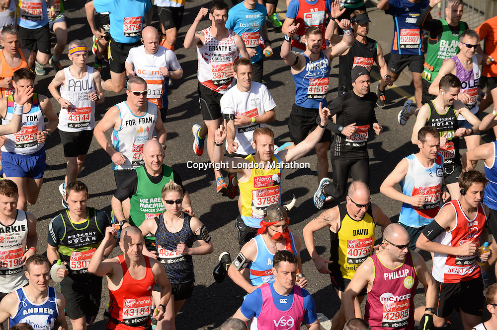 The mass of runners cross the start line at the Red Start of The Virgin Money London Marathon 2014. Sunday 13 April 2014<br /> <br /> Photo: Tom Lovelock/Virgin Money London Marathon<br /> <br /> media@london-marathon.co.ukThe Virgin Money London Marathon 2014<br /> Red Start<br /> Picture Tom Lovelock