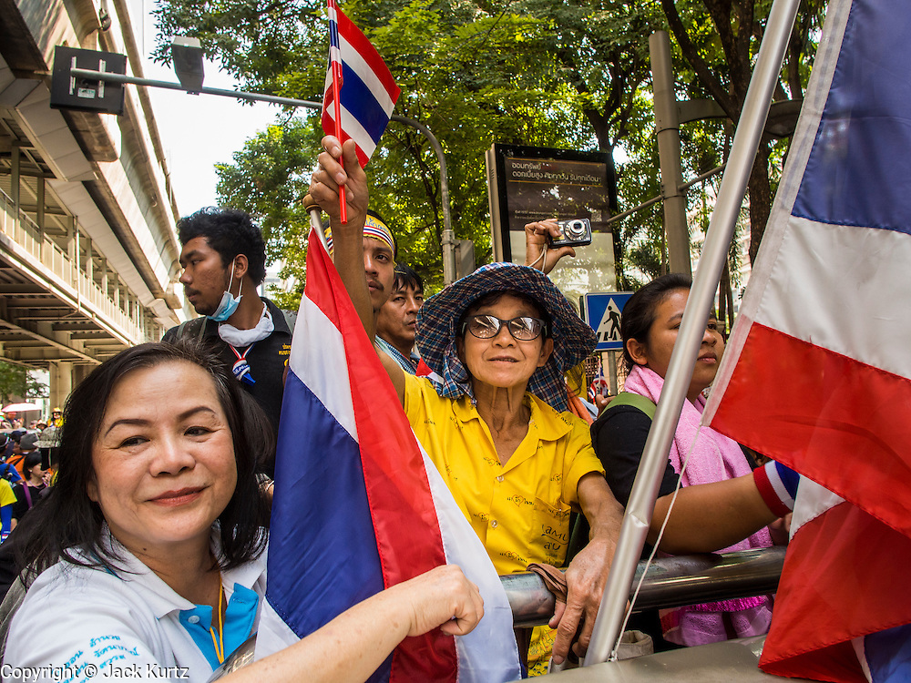 04 DECEMBER 2013 - BANGKOK, THAILAND:  An anti-government protestors drive away from a protest at police headquarters. Several hundred anti-government protestors tried to occupy Royal Thai Police Headquarters on Rama I Road in central Bangkok Wednesday. The protest was one of the continuing protests against the government of Prime Minister Yingluck Shinawatra. Police commanders allowed protestors to tear down police barricades and ordered riot police to lay down their shields. Protestors then chanted anti-government slogans and called on police to turn against the government before forming a motorcade and leaving the area. Anti-government protests have gripped Bangkok for nearly a month and protestors vow to continue their actions. Protests Wednesday were much smaller and more peaceful than protests earlier in the week.     PHOTO BY JACK KURTZ