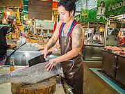 09 DECEMBER 2014 - THONBURI, BANGKOK, THAILAND: A fish seller cuts up a fish in his market stall in the Thonburi section of Bangkok.    PHOTO BY JACK KURTZ