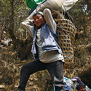 A porter with a doko and tump line carries his load through the Colu-Khumbu region of Nepal.