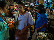 11 OCTOBER 2016 - UBUD, BALI, INDONESIA: People walk through the morning market in Ubud. The morning market in Ubud is for produce and meat and serves local people from about 4:30 AM until about 7:30 AM. As the morning progresses the local vendors pack up and leave and vendors selling tourist curios move in. By about 8:30 AM the market is mostly a tourist market selling curios to tourists. Ubud is Bali's art and cultural center.      PHOTO BY JACK KURTZ