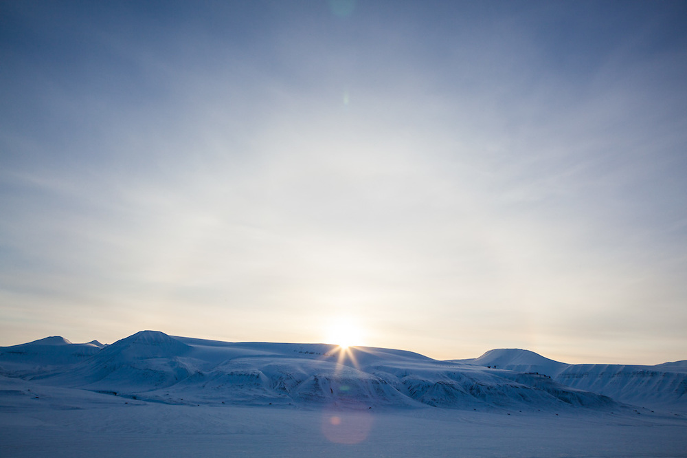 The sun appears briefly over Breinosa and Adventdalen, Svalbard. The parabolic radar antennas at the European Incoherent Scatter Scientific Association (EISCAT) facility are visible on the right.