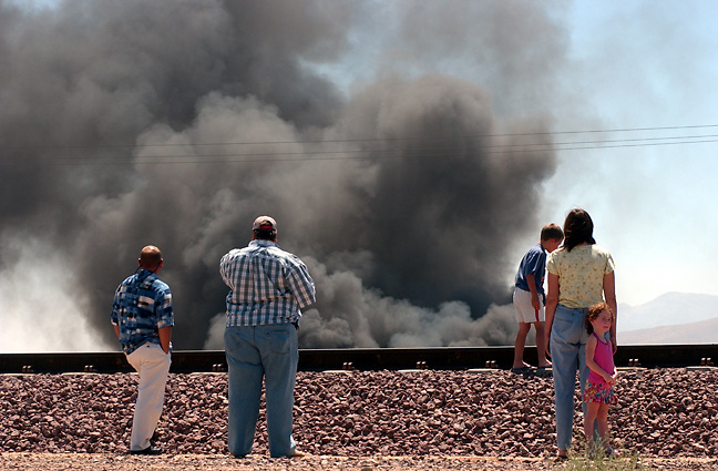 Michael Stenerson / Staff Photographer.Traffic near the intersection of Hesperia Rd and Santa Fe lined up along the railroad tracks to watch smoke billow from a scrapyard blaze that began around 10:30 AM in Hesperia Wednesday, July 6, 2005. The blaze emitted a cloud of smoke that could be seen for miles around and engulfed around 40-50 scrap automobiles. At least 5 firetrucks were on hand to help fight the fire.