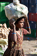 Young girl carrying food in Old Delhi at Daryagang market, India
