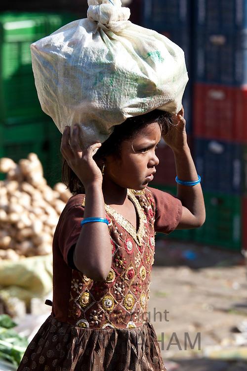 Young girl carrying food in Old Delhi at Daryagang market, India