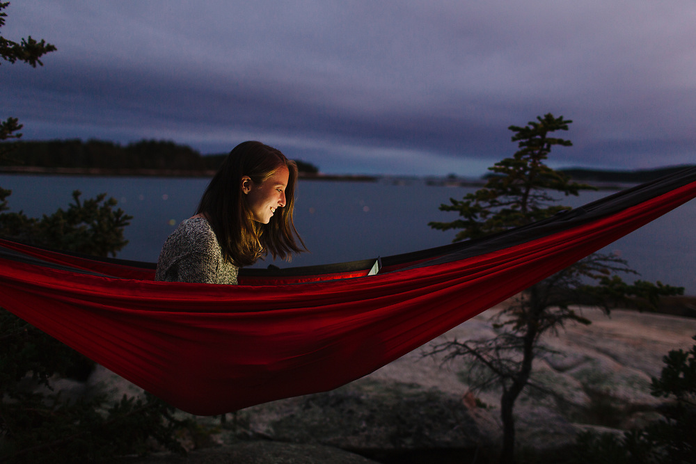 Young woman in hammock with laptop near ocean.