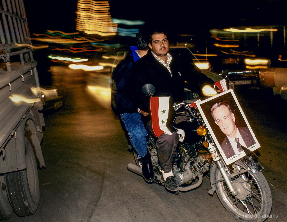'PERSONALITY CULT OF ASSAD', YOUTHS RIDING MOTORBIKE WITH POSTER PORTRAIT OF ASSAD ATTACHED TO THE FRONT DURING THE REFURENDUM CAMPAIGN, DAMASCUS, DECEMBER 1991