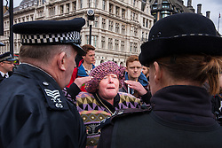 "Parliament Square, London, October 22nd 2014. Protesters from ""Occupy Democracy"" continue their demonstration against what they say is the hijacking of Britain's democracy by capitalism, where big business is allowed to trample people's rights. Having earlier been removed from Parliament square on grounds that they had damaged the threadbare lawn, they continue to demonstrate outside the closed off space. PICTURED: A woman from Occupy Democracy engages in an exchange of views with police officers."