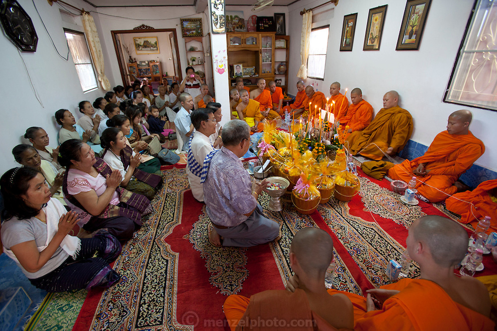 Buddhist ceremony after the cremation ceremony with relatives and monks in the family home in honor of Mr. Voua Sy Amkha, 63, a propaganda official for the Lao government in Luang Prabang, Laos, who died of a stroke. His funeral was held over a series of days—first at home with family and monks in Ban Navieng Kham village, a suburb of Luang Prabang, then cremation at the central crematorium site in Ban Vieng Mai, and then again at home a few days after the cremation ceremony.
