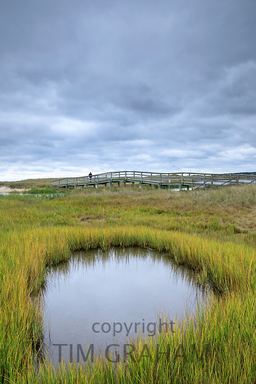 Lone person on wooden footbridge walkway at Ridgevale Beach, Nantucket Sound, Cape Cod, New England, USA