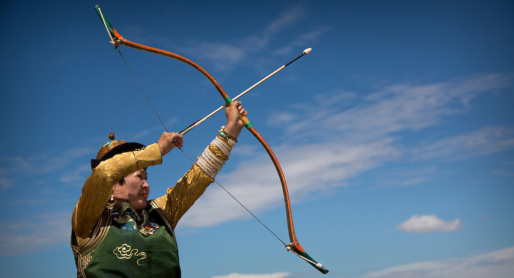 A Mongolian women shows off her archery skills during the Naadam Festival at the Three Camel Lodge in the Gobi Desert of Mongolia on July 31, 2012. Archery is one of the ?Three Manly Sports? practiced during the Naadam Festival. © 2012 Tom Turner Photography.