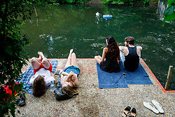 © Licensed to London News Pictures. 25/05/2017. London, UK. People sunbathe in Hampstead Heath Mixed Bathing Pond in north London as temperatures hit 29C on Thursday 25 May 2017. Photo credit: Tolga Akmen/LNP