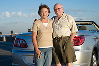 Senior couple standing in front of car, portrait