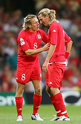 CARDIFF, WALES - Wednesday, September 8, 2004: Wales' Robbie Savage is consoled by Craig Bellamy as he walks off the pitch in tears after being sent off against Northern Ireland during the Group Six World Cup Qualifier at the Millennium Stadium. (Pic by David Rawcliffe/Propaganda)