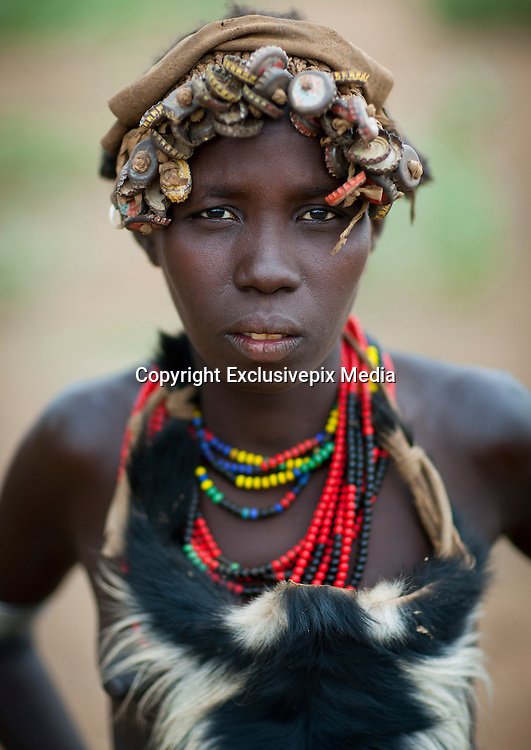 """Ethiopian Tribe Recycles Modern World's Discards Into Fashion Accessories<br /> <br /> The Daasanach are a semi-nomadic tribe numbering approximately 50,000 individuals who live in the Omo Valley in southern Ethiopia. In the past, the tribe roamed from place to place herding livestock around open areas according to the seasons and the changing availability of water. But over the last fifty years, having lost the majority of their lands, they have also grown dependent to agriculture. Like many tribes in the region, the Daasanach have moved to areas closer to the Omo River, where they attempt to grow enough crops to survive.<br /> <br /> French photographer Eric Lafforgue has spent several years documenting the life and culture of these people, and how they have changed under the influence of modern manufactured goods. An interesting fashion trend amongst the Dassanach is their elaborate headgear, which they make from the strangest of materials — bottle caps, wristwatches, hairclips, and other discarded pieces of plastic and metal.<br /> The Daasanach spend months collecting bottle caps and scratching around for cash to pay for broken watches, which the women makes into jewelry and wigs. These are worn by both men and women, young and old.<br /> <br /> """"Younger girls and children get the most basic version of the wig, while the oldest women are treated to the heaviest numbers with the most embellishment,"""" wrote The Daily Mail. """"Men are only allowed to wear the bottle top wigs until they marry - after that, they create small clay headpieces decorated with a colourful harlequin pattern and enlivened with a feather, although the latter is only allowed after a hunt or a successful clash with an enemy.""""<br /> <br /> """"The young men love to wear necklaces and earrings while the girls have bigger muscles because they do the most difficult work like carrying water,"""" Eric Lafforgue told the newspaper.<br /> <br /> To prevent their headgears from getting spoiled while they sleep"""