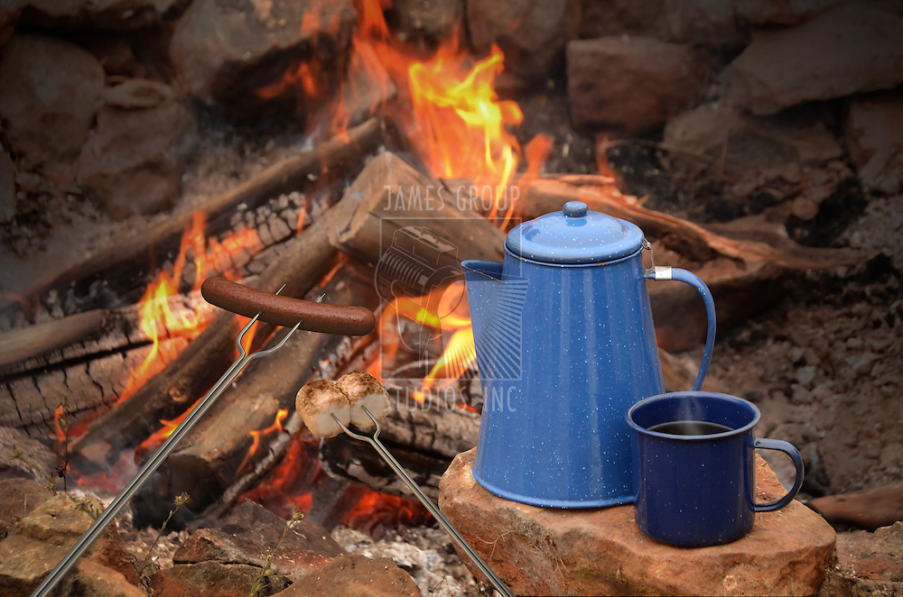 hot dog on a long fork over a fire next to an enamel coffee percolator and mug full of coffee.