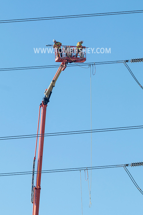 Town of Wawayanda, New York - Men on a lift work on Marcy-South transmission lines on Sept. 25, 2016. The 345,00-volt lines run between 160-foot towers.