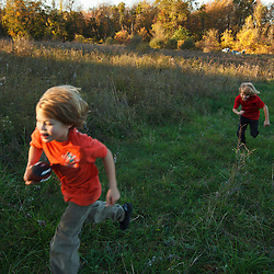 Two nine year old boys run in a field at Elmwood Farm in Hopkinton, Massachusetts. Fall.