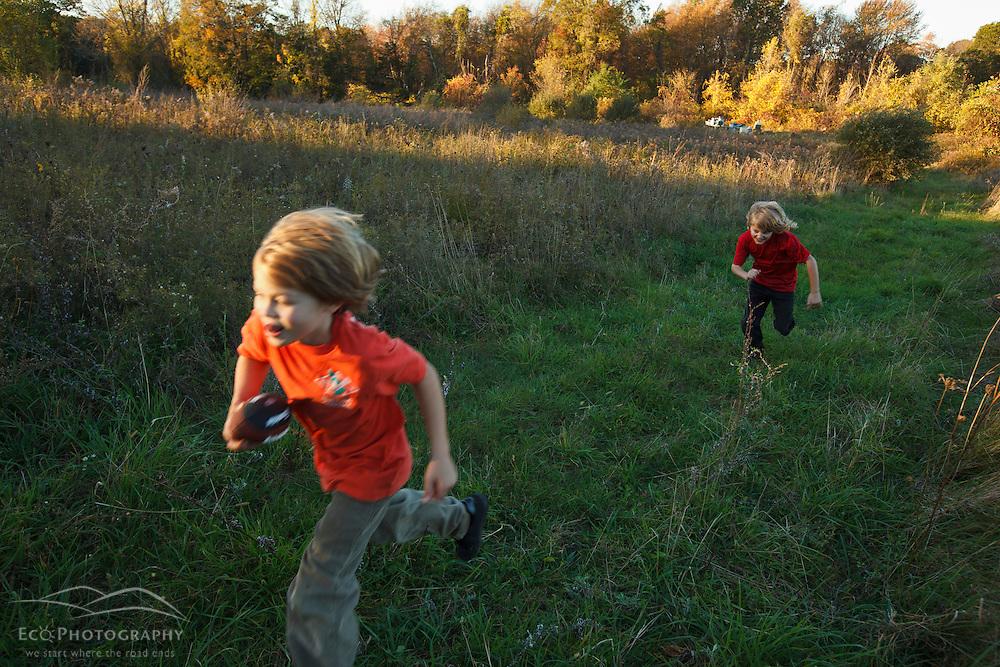 Two nine year old boys run in a field at Elmwood Farm in Hopkinton, Massachusetts. Fall.