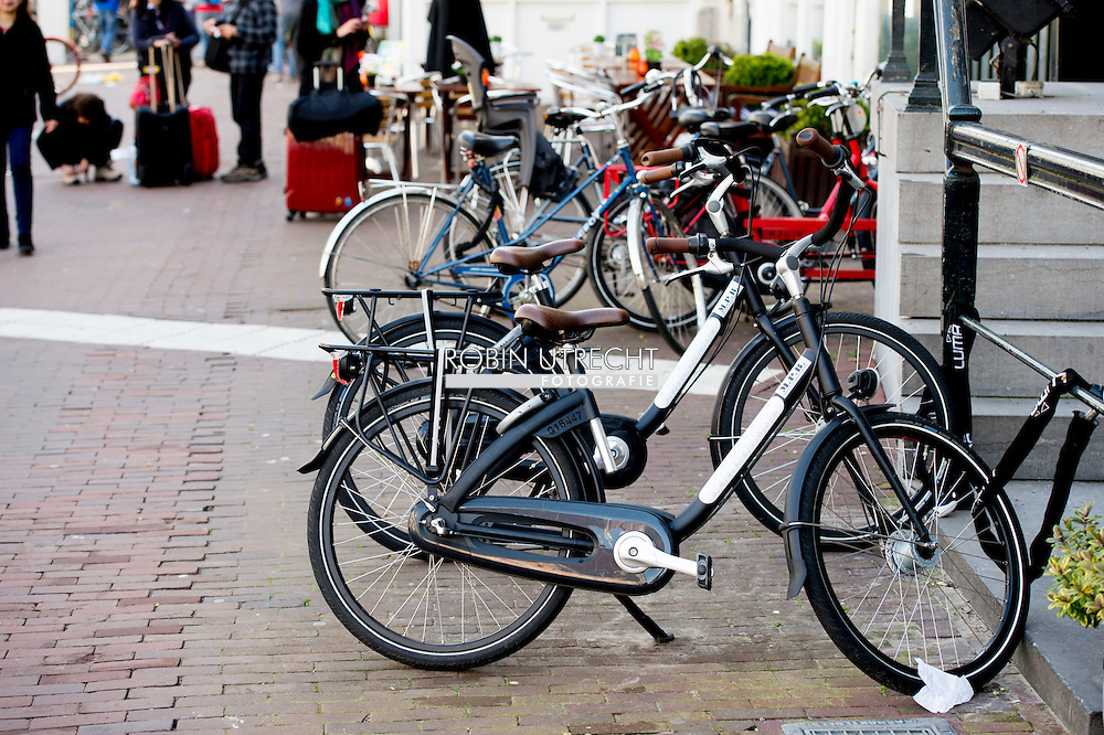 amsterdam - fietsen staan op straat in amsterdam . toerist  toeristen copyright robin utrecht