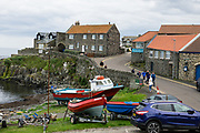 Craster village harbor. Walk 3 miles round trip from Craster village to the impressive ruins of 1300s Dunstanburgh Castle on the coast of Northumberland, England, United Kingdom, Europe. The castle was built by Earl Thomas of Lancaster between 1313-1322 on existing earthworks of an Iron Age fort. Thomas was a short-lived leader of a baronial faction opposed to King Edward II. This strategic northern stronghold never recovered from seiges during the Wars of the Roses 1455-1487 after it changed hands several times between rival Lancastrian and Yorkist factions. King James I sold the fort into private owndership in 1604. Dunstanburgh Castle is now owned by the National Trust and run by English Heritage.