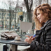 Young blonde woman taking a break at a coffee bar. Looking away from cmera.Taking notes on a tablet and writing on her calendar