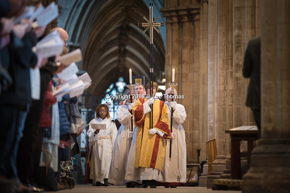 Lichfield Cathedral, Lichfield, Staffordshire, UK. 29th March 2018. The Bishop of Lichfield together with hundreds of clergy and worshippers join together at Lichfield Cathedral to commemorate Maundy Thursday. Pictured: Caroline Payne (holding cross) leads the procession at Lichfield Cathedral. // Lee Thomas, Tel. 07784142973. Email: leepthomas@gmail.com  www.leept.co.uk (0000635435)