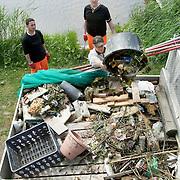 Nederland Den Haag 13 mei 2009 20090513 Foto: David rozing .Nieuwbouwwijk Wateringse Veld, medewerkers schoonmaak dienst vissen afval uit het water. opruimen,. opruimdienst, net, netten, cvisnet  Foto: David Rozing