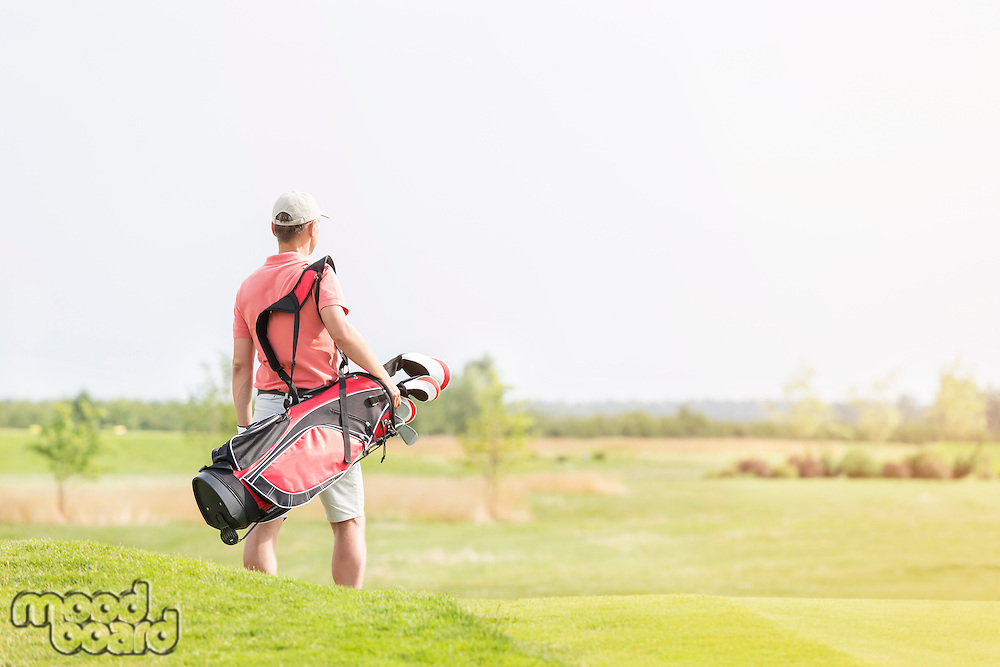 Rear view of man carrying golf club bag while walking at course