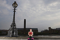 Triathlon athlete standing by river embankment London England