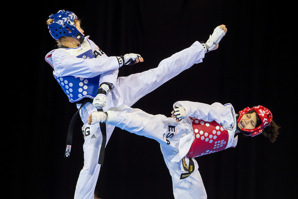 Celina Proffen (L) of Argentina and Vanessa Vasquez of El Salvador trade kicks during their repechage contest in the women's Taekwondo -57kg division of at the 2015 Pan American Games in Toronto, Canada, July 20,  2015.  AFP PHOTO/GEOFF ROBINS