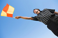Soccer linesman waving flag portrait low angle view