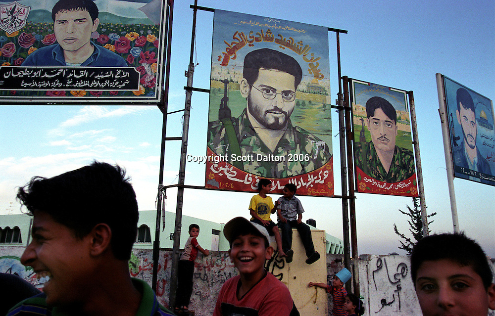 "Youths gather on a street corner in Gaza City where paintings have been hung in honor of the ""Martyrs"" that have died fighting the Israelis or in suicide bombings. (Photo/Scott Dalton)"